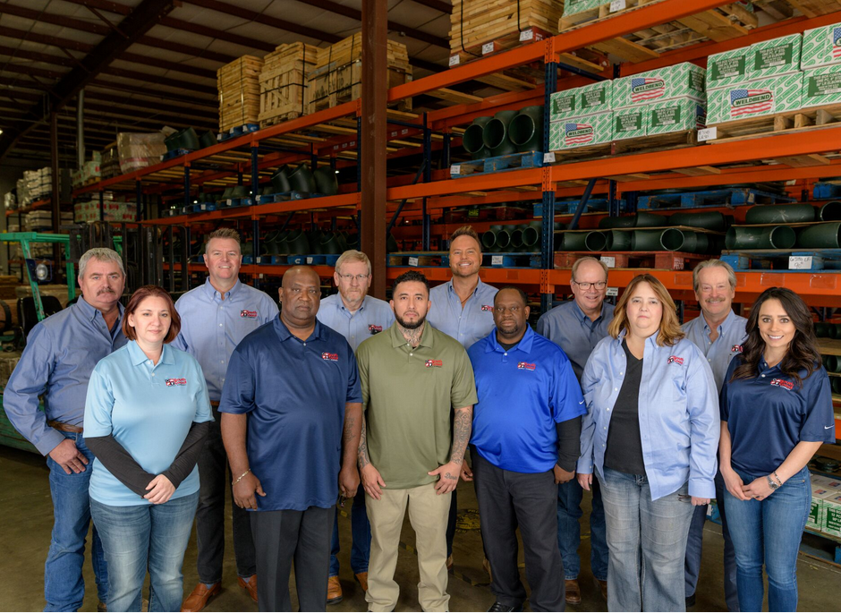 Employees of South Coast Supply Company standing in front of shelves with boxes in a warehouse.